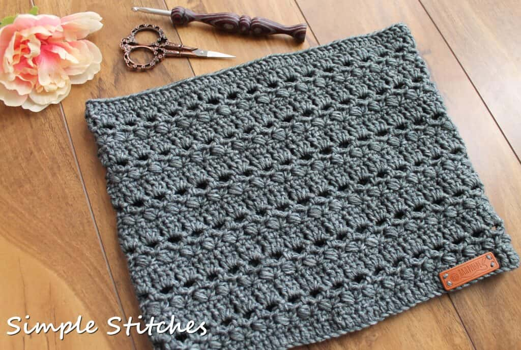 Flat lay of gray crochet cowl, called the Brimstone Cowl.