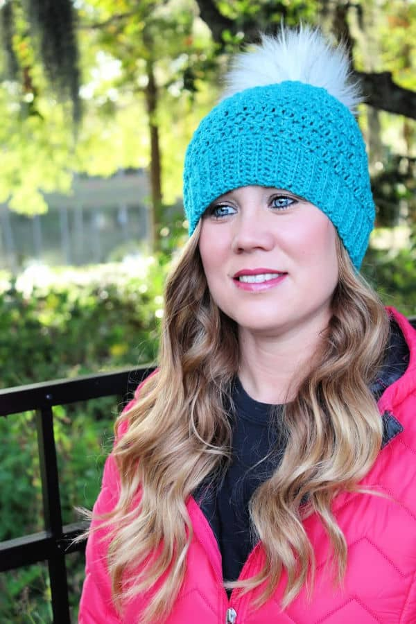 Woman wearing a teal colored crochet hat, called the Edgewater Hat.