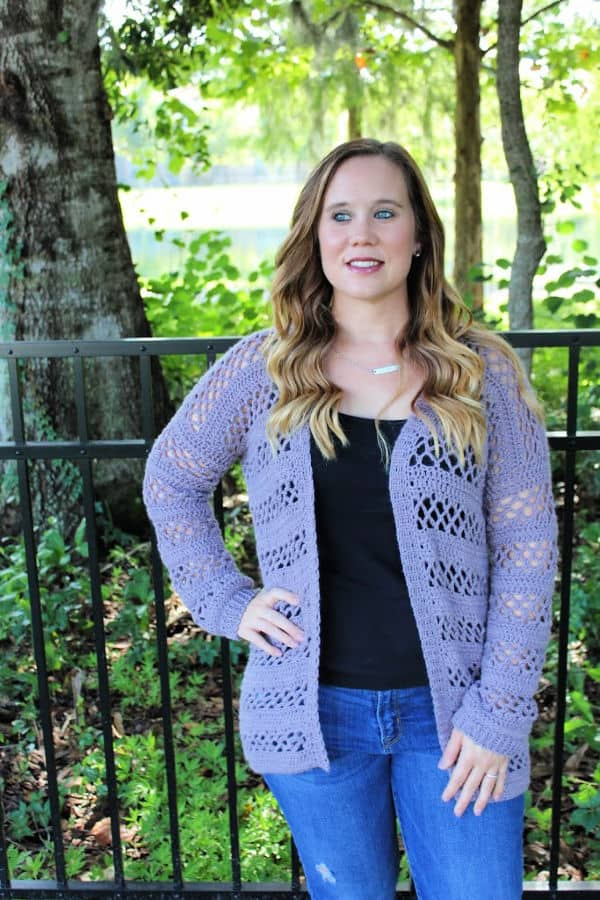 Woman wearing a purple crochet cardigan, called the Magnolia Cardigan.