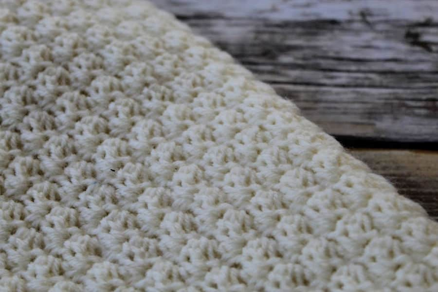 Close up of a cream colored crochet lap blanket, called the Ferguson Lap Blanket.