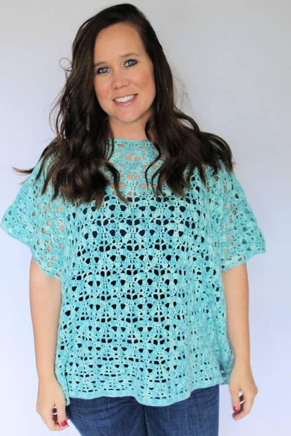 Woman wearing a blue crochet poncho, called the Bindi Poncho.
