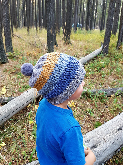 Boy wearing a crochet slouch hat pattern with a pom pom on the top, called the Savannah Slouch.