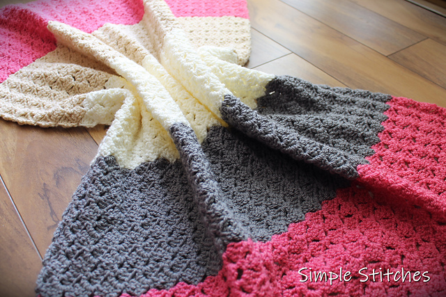 A crochet throw, called the Dallas Blanket, laid out on the floor. The blanket is pink, gray, and cream colors.