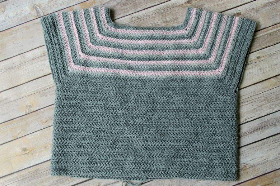 A flat lay of a raglan crochet sweater pattern in progress.