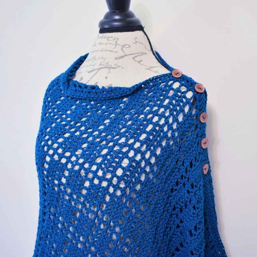 Teal poncho style wrap with buttons down the shoulder.