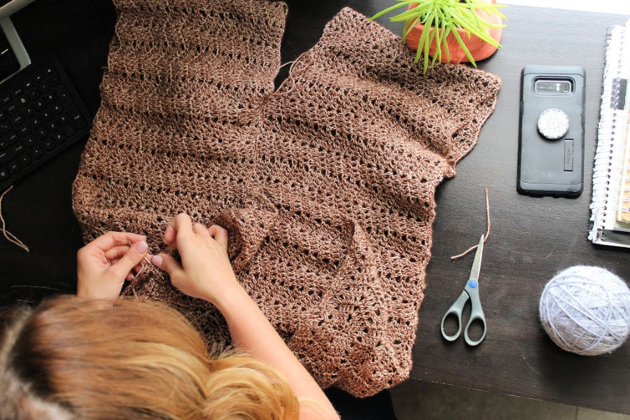 Sewing two crochet pieces together.
