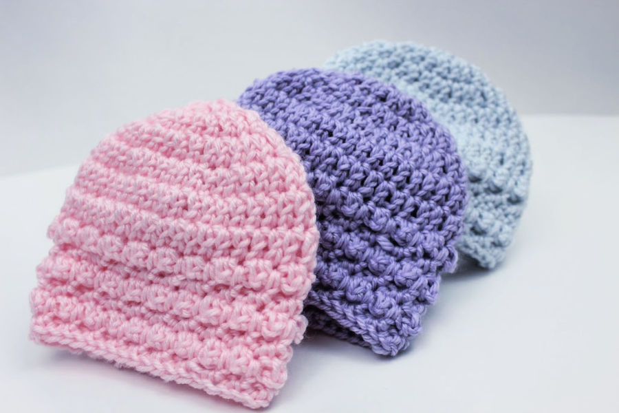 Three Little Textures Newborn Beanies displayed in colors light blue, purple, and pink.