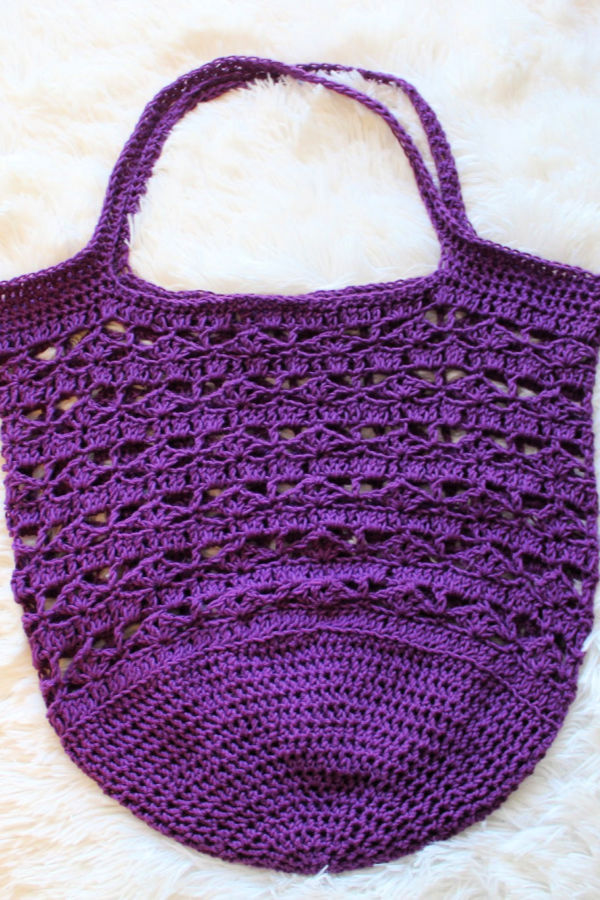 Purple crocheted market bag laid flat.