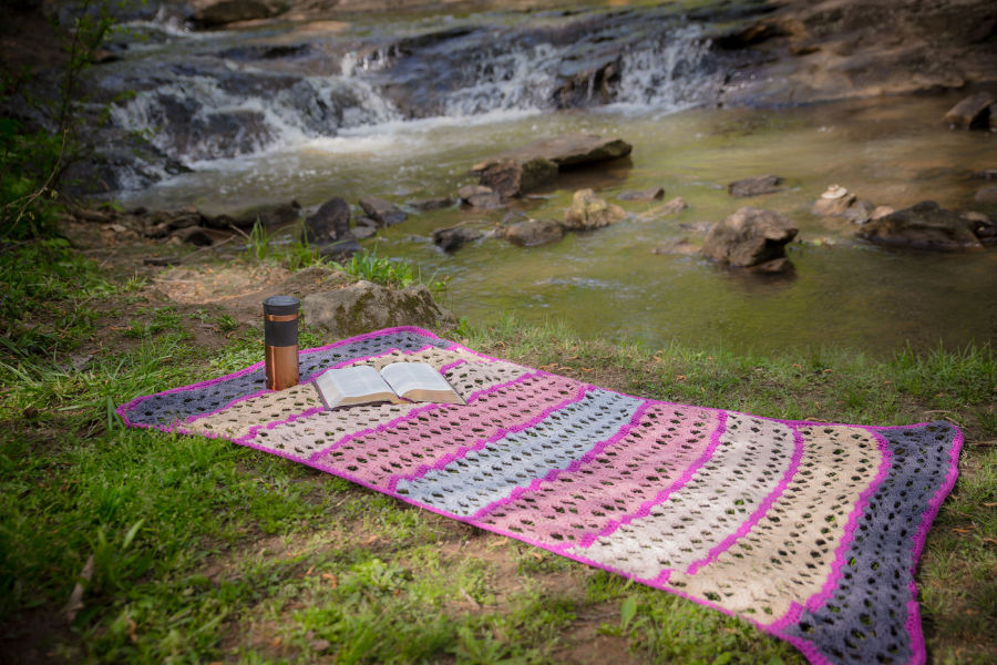 Serenity Blanket spread out on the grace with a bible and a travel mug on it in front of a stream.