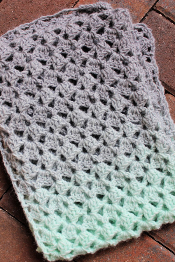 Flat lay of mint green and light gray scarf called the Delightful Scarf.