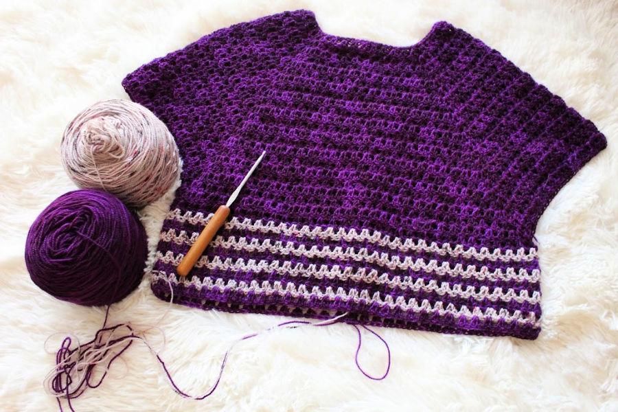 A flatlay of the Leilani Raglan Tee crochet top with a crochet hook and yarn beside it.