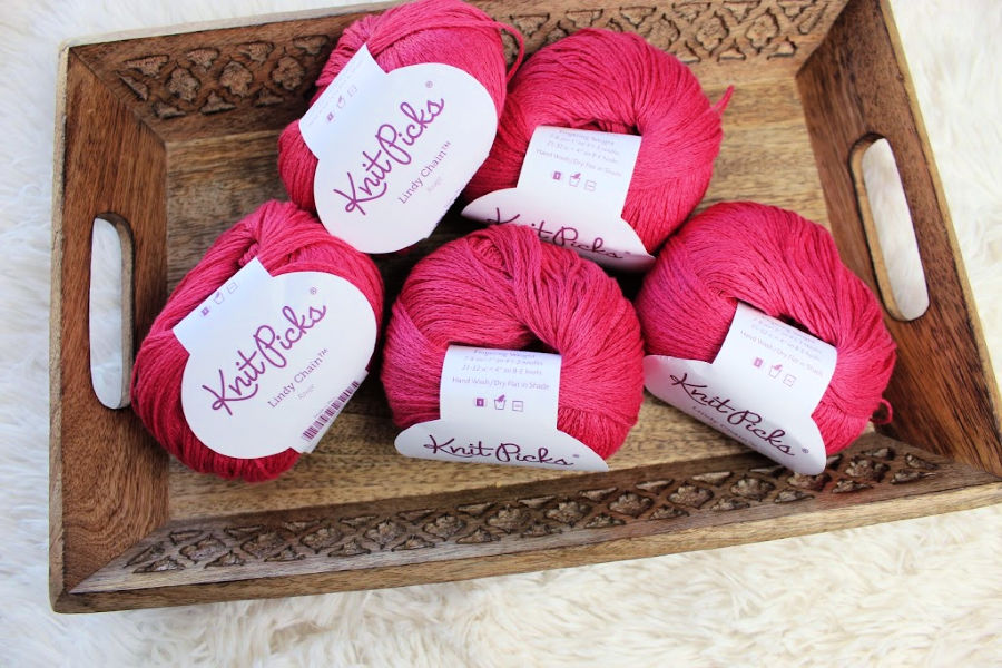 Five balls of Lindy Chain yarn in a pink colorway called Rogue.