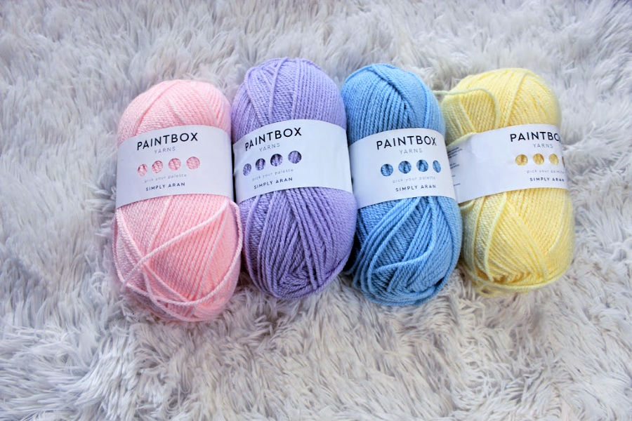 Paintbox Yarn Simply Aran lined up in colors pink, purple, blue, and yellow.