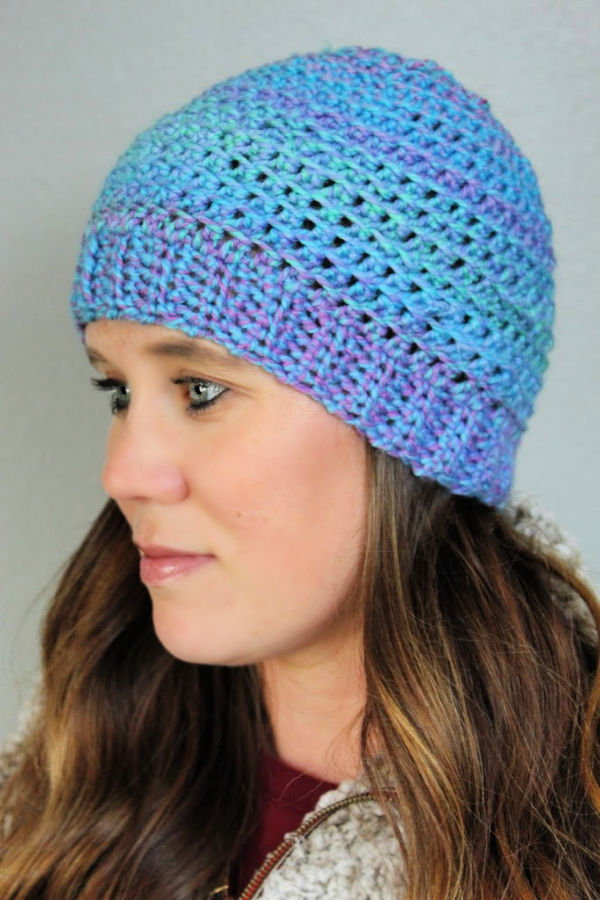 Woman wearing pink and blue crocheted hat called the KJ Hat.