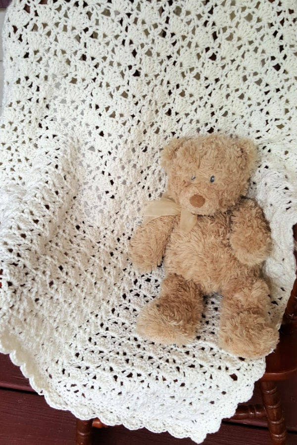 Sarah Baby Blanket laid over a small rocking chair with a stuffed teddy bear sitting on the chair.