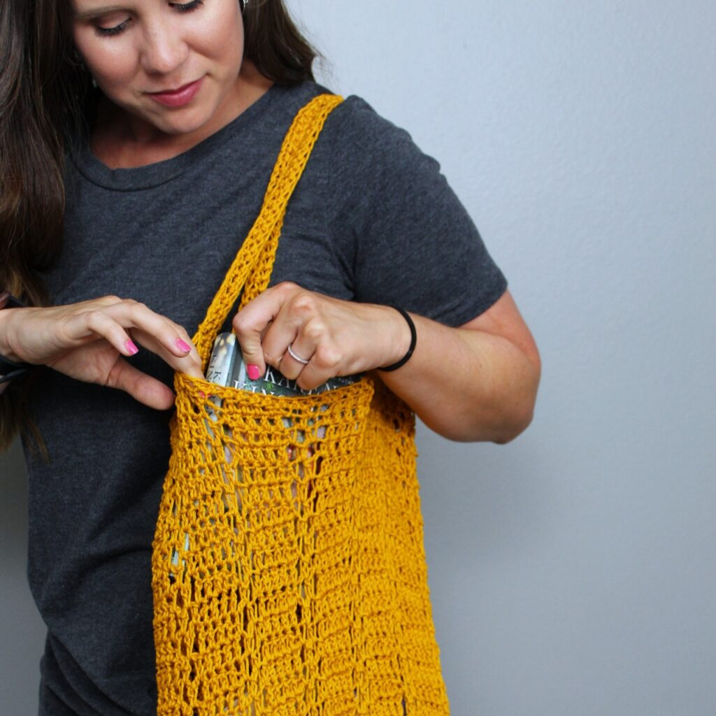 Woman pulling a book out of a crocheted bag, called the Sabre Bag.