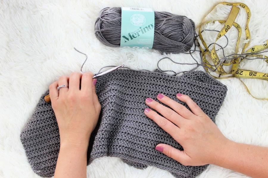 A woman crocheting with gray yarn.