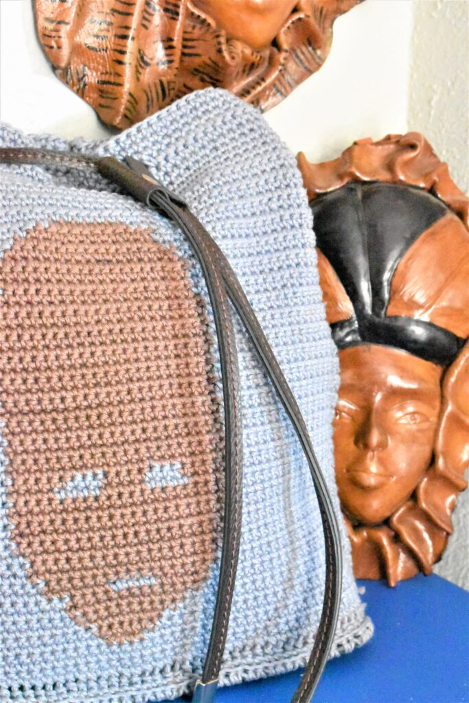 Close up of bag next to a real Haitian mask.