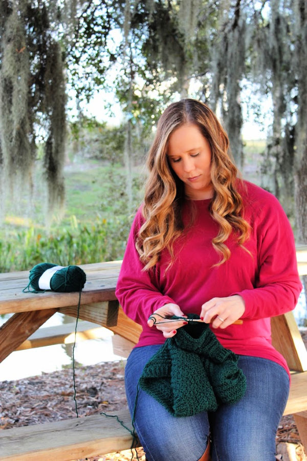 Woman crocheting on a park picnic table.
