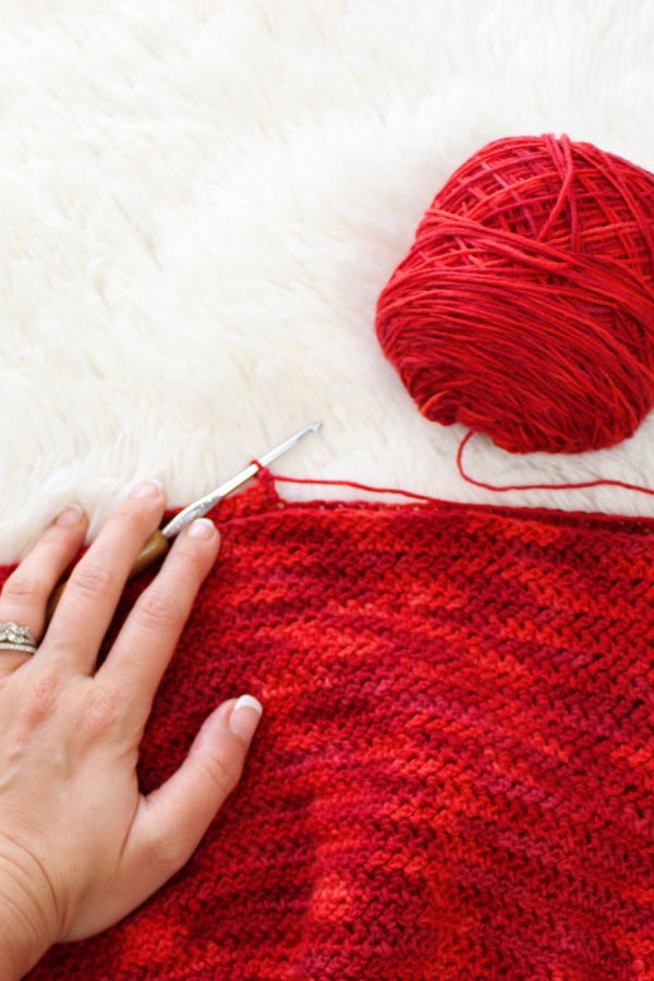 Yarn and crochet hook with woman's hand over it. Switching out yarn and crochet hook can help alleviate crochet pain.