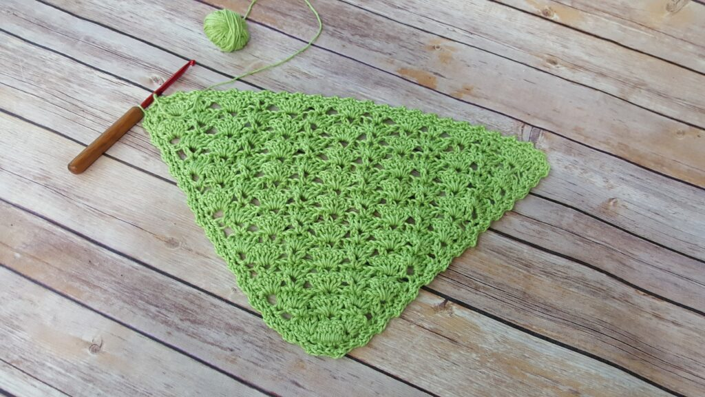 Flat lay of the beginnings of a crocheted triangle shawl, called the Cecilia Shawl.