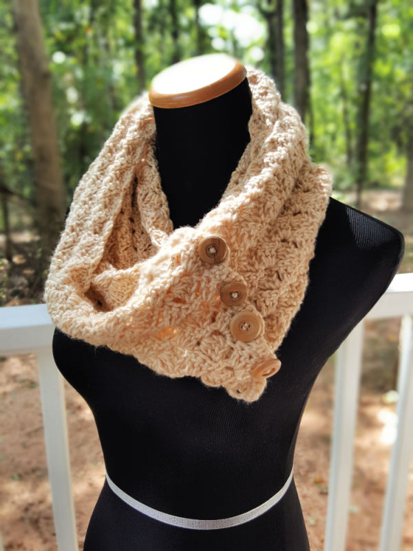 Cream colored crochet infinity scarf with buttons, called the Dallas Scarf.