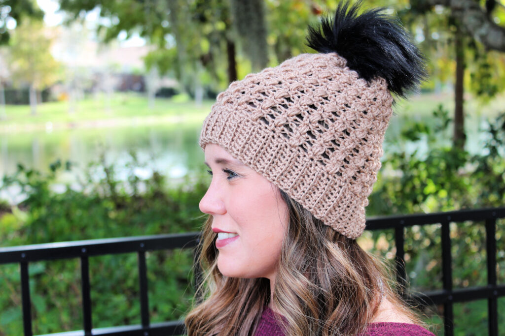 Woman wearing a taupe colored crochet hat, called the Appleton Hat.