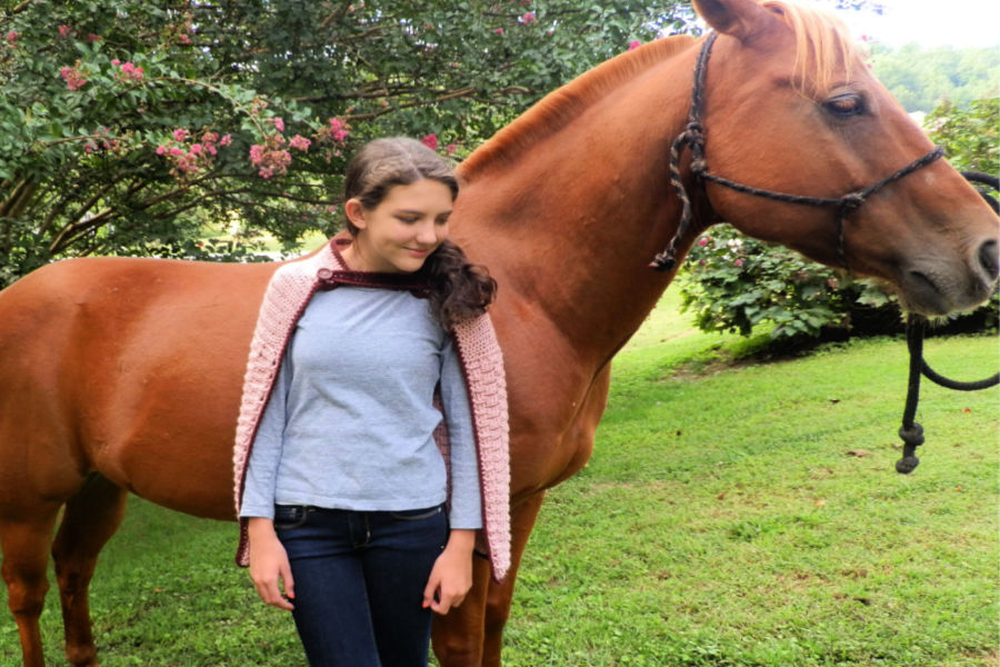 Girl standing in front of a brown horse, wearing a pink crochet cape - called the Enchanted Dreams Cape.