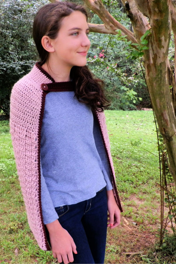 Girl wearing a pink crochet cape, called the Enchanted Dreams Cape.