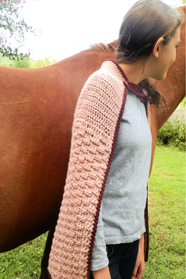 Side view of woman wearing a pink crochet cape, called the Enchanted Dreams Cape. She is standing next to a brown horse.