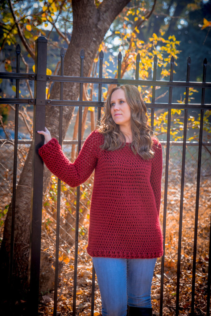 Woman wearing a crochet sweater in dark red, called the Raleigh Tunic.