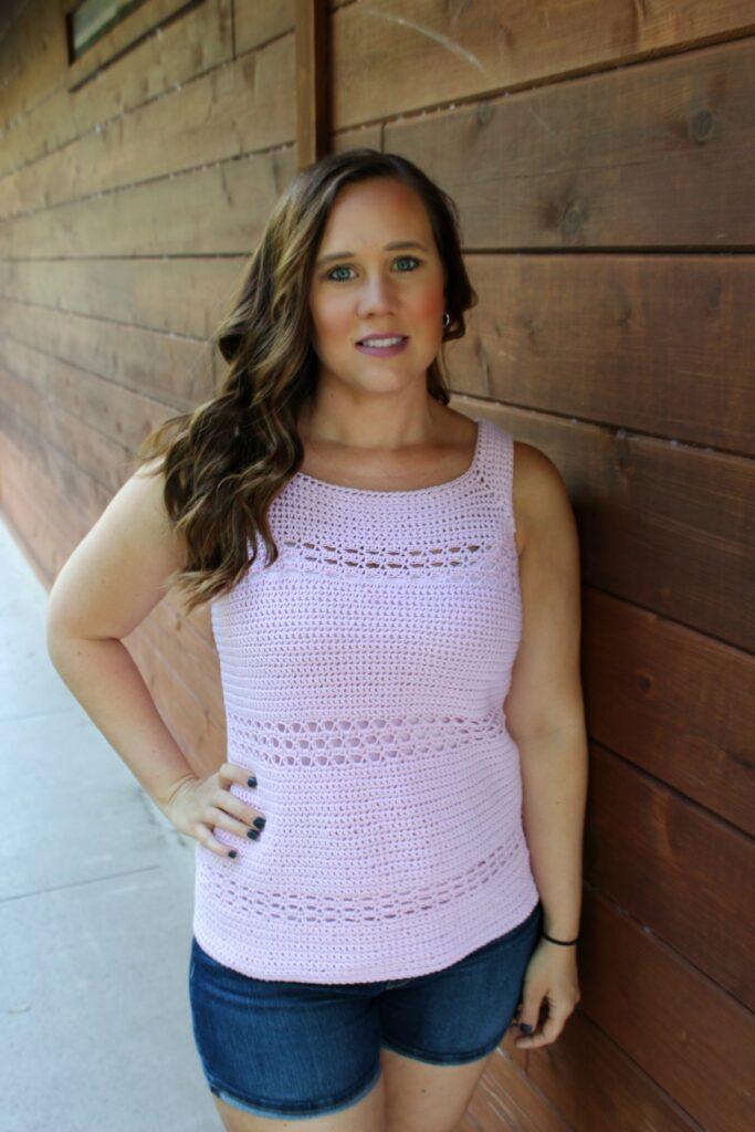 Woman wearing pink crochet tank top, called the Blushing Eyelet Tank.