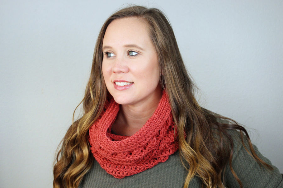 Woman wearing a coral colored crochet cowl pattern, called the Catherine Cowl.