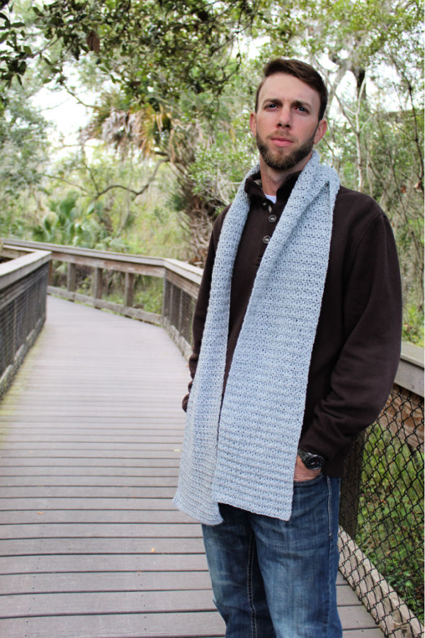 Man wearing a gray crochet scarf.