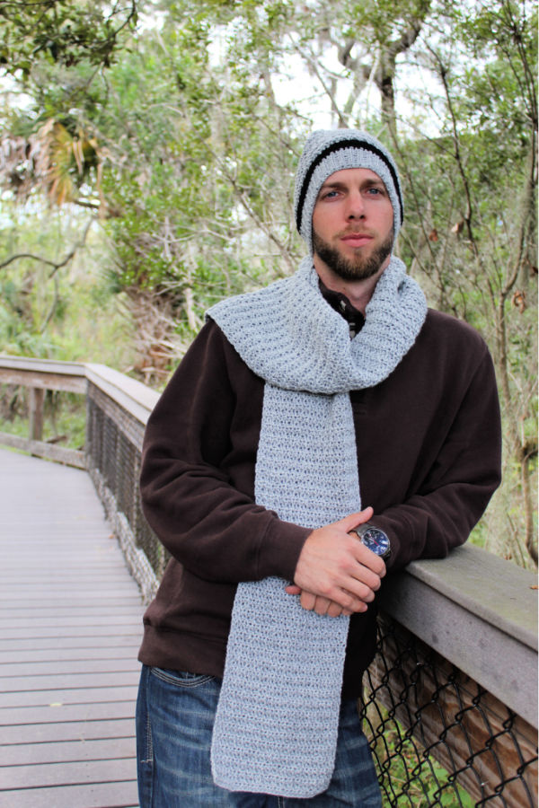 Man wearing a gray crochet hat and scarf.