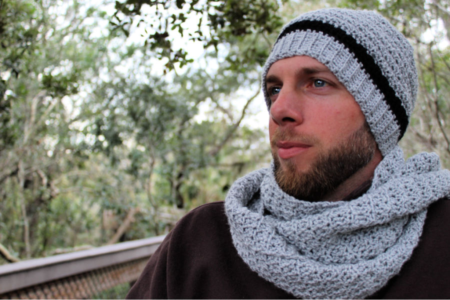 Man wearing a grey crochet hat and scarf, called the Dude Hat and Scarf Set.