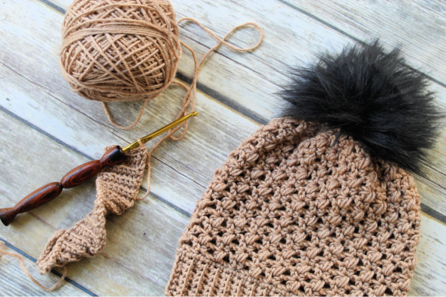 Photo of a taupe colored crochet hat, called the Appleton Hat, with a cake of yarn and crochet hook next to it.