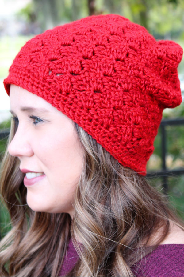 Woman wearing a red crochet slouchy hat, called the Dallas Hat.