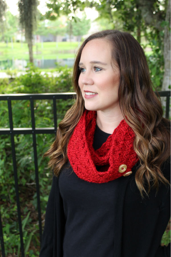 Woman wearing a red crochet infinity scarf with buttons, called the Dallas Scarf.