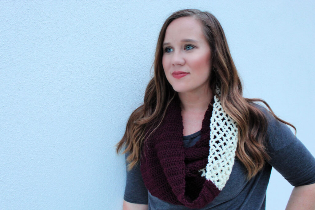 Woman wearing a maroon and cream colored crochet infinity scarf, called the Magnolia Scarf.