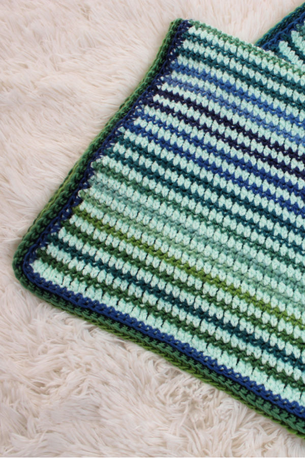 Close up of the preemie crochet blanket, called the Friendship Blanket. The blanket is mint green with blue and green stripes.