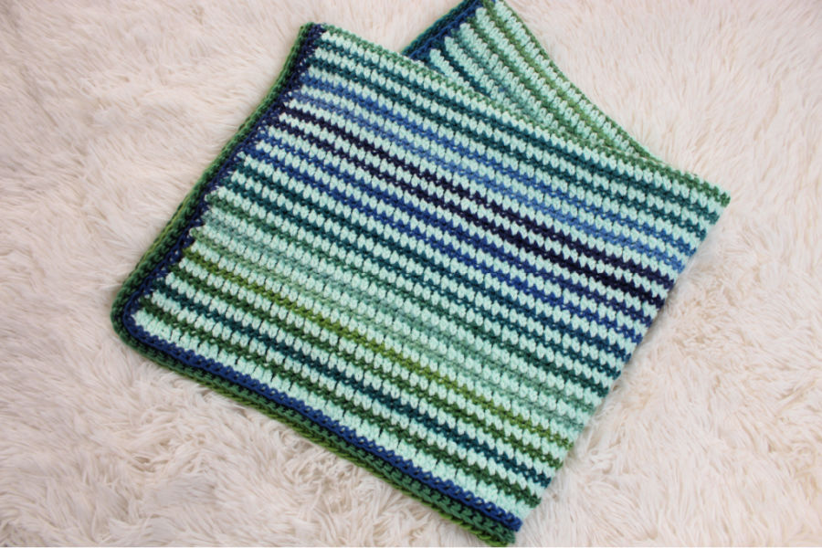 Photo of the preemie crochet blanket called the Friendship Blanket. The blanket is mint green with blue and green stripes.