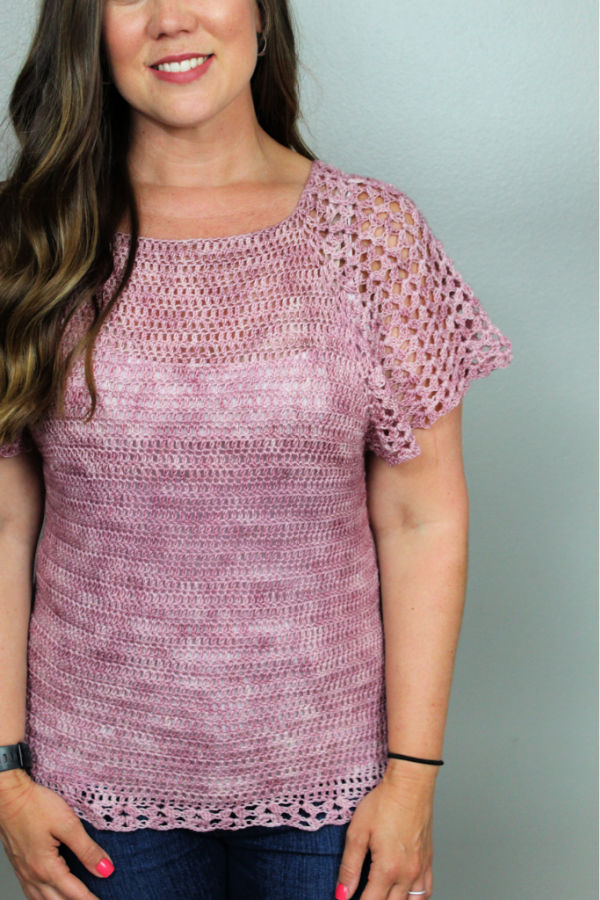 Close up of woman wearing a pink summer crochet top called the Rosie Tee.