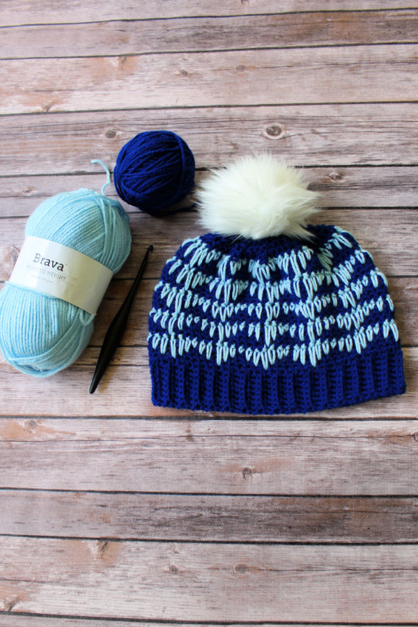 Flat lay of the Easy Crochet Hat, called the Heartbeat Hat, with crochet hook and blue yarn lying next to it.