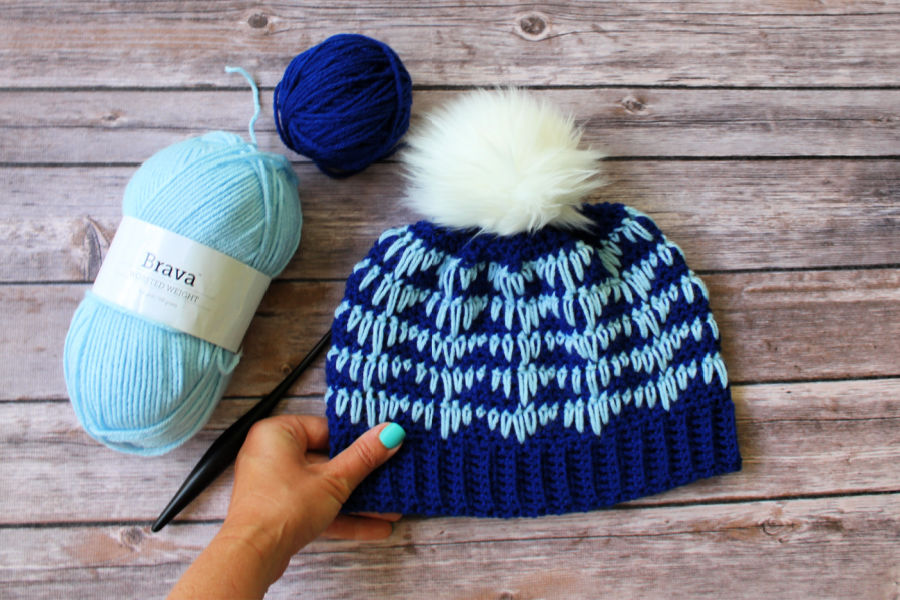 Easy Crochet Hat Pattern called the Heartbeat Hat laid flat with crochet hook and blue yarn lying next to it.