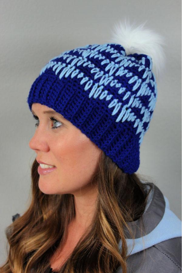 Woman wearing blue crochet hat called the Heartbeat Hat.