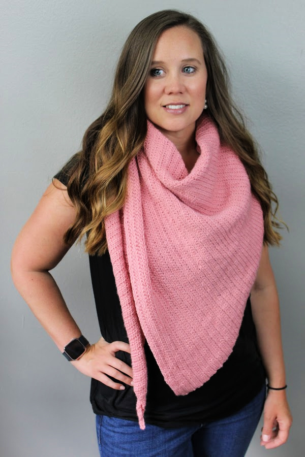 Woman wearing pink crochet shawl called the Sydney Shawl.