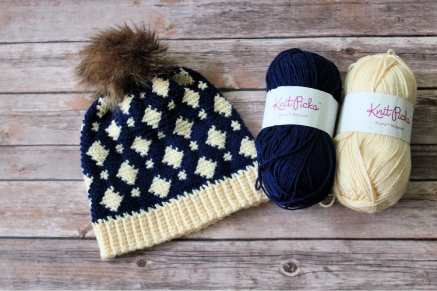 Flat lay photo of a fair isle crochet hat, called the Gatlinburg Hat, and two skeins of yarn in navy blue and cream colors.