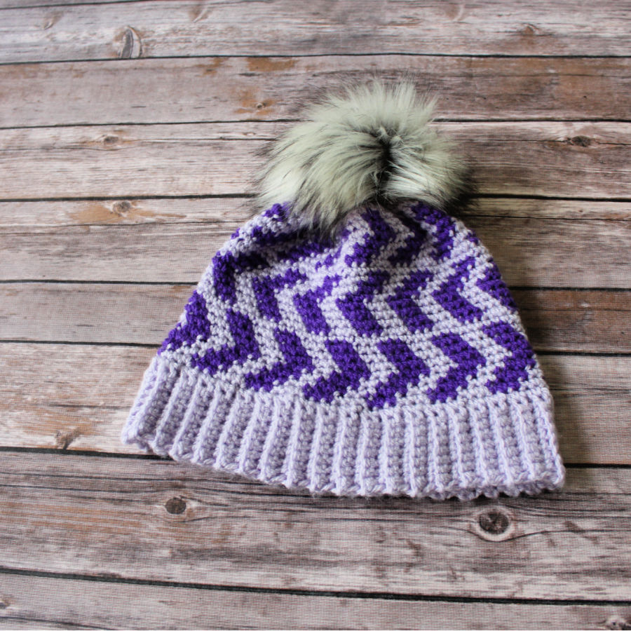 Flat lay of crochet hat in dark and light purple, called the Halifax Hat.