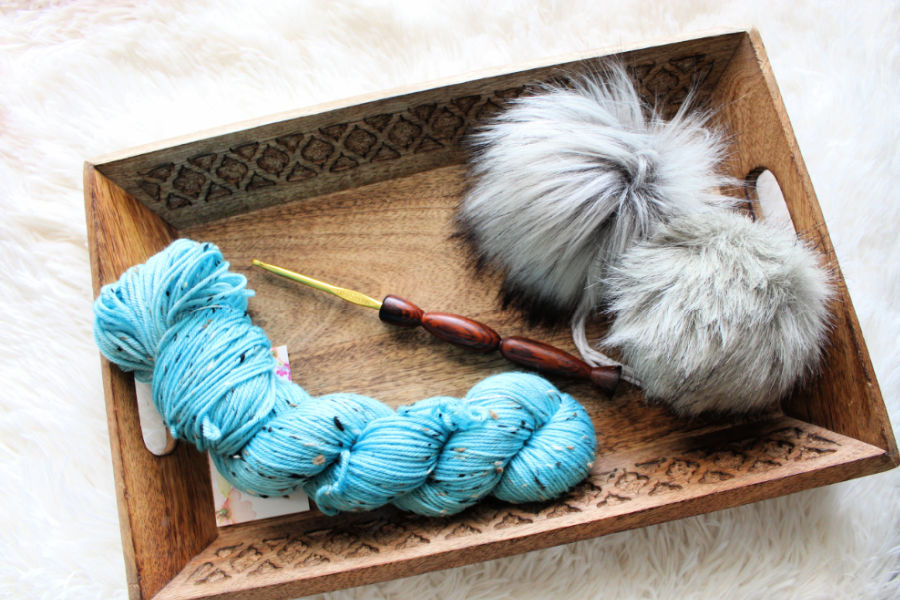Photo of a blue skein of yarn, a handmade crochet hook, and 2 faux fur poms.